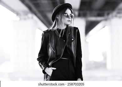 fashion model in sunglasses, hat and black leather jacket posing outdoor. Black and white image