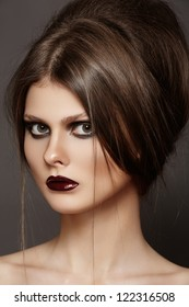 Fashion model with tousled hair, make-up. Portrait of young fashion woman with punk rock hairstyle, dark make-up