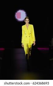 Fashion model walks the runway in yellow pantsuit