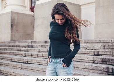 Fashion model wearing blank black long sleeve tshirt posing in the city street. Casual everyday clothing style, t-shirt mockup.