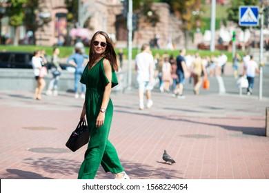 Fashion model wearing green overall posing outdoor. Young beautiful brunette caucasian woman walking summer streets. Beautiful girl, urban portrait.