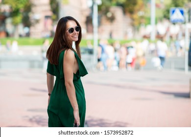 Fashion model wearing green overall posing outdoor. Young beautiful brunette caucasian woman walking summer streets. Beautiful girl, urban portrait.