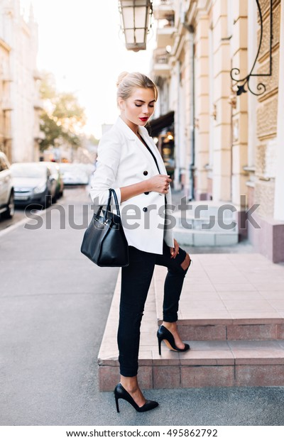 Fashion model in white jacket on stairs on street. She wears high heels, looking down