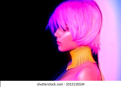 Fashion model woman in colorful bright neon lights, portrait of beautiful party girl with trendy make-up and haircut. Art design of disco dancer, colorful make up. Over vivid background