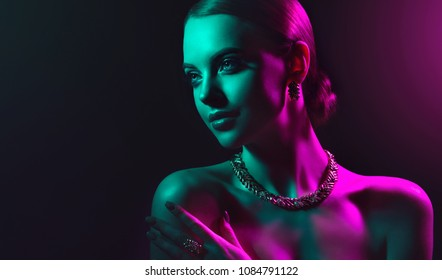 Fashion model woman in colorful bright lights with trendy makeup . Beautiful girl with set jewelry .   Woman in a necklace with a ring, earrings and a bracelet. Beauty and accessories.
