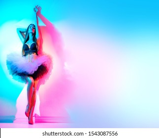 Fashion model woman in colorful bright neon lights dancing in night club in tulle skirt, high heels. Full length Portrait of beautiful sexy seductive dancer girl in UV. On colourful vivid background