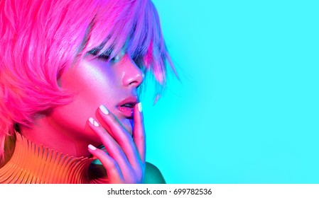 Fashion model woman in colorful bright lights, portrait of beautiful party girl with trendy make-up, manicure and haircut. Multicolored Art design, colorful make up. Over colourful vivid background.