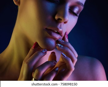 Fashion model woman in colorful bright lights posing in studio, portrait of beautiful sexy girl with trendy make-up and manicure. Art design, colorful make up. Over colorful vivid background