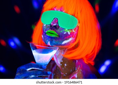 Fashion model woman drinking alcoholic cocktail in neon light, disco night club. Beautiful dancer model girl colorful bright fluorescent make-up