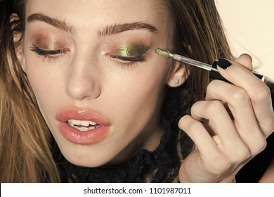 Fashion model woman fece close up. Face woman wiht happy emotion. Woman with long hair and fashionable makeup. Girl put eyeshadow on eyes with brush, new technology. Beauty salon and fashion look