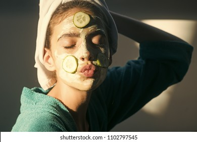 Fashion model woman fece close up. Face woman wiht happy emotion. Cosmetics, cosmetology, dermatology. Girl or woman face with cucumber mask, towel on head. Beauty salon concept. Skin and hair care