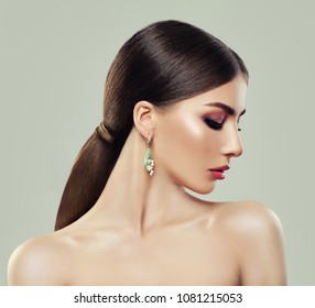 Fashion Model Woman with Makeup, Healthy Hair and Earrings with Jewelry Pearls and Green Gem