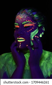 Fashion model woman in neon light, portrait of beautiful model girl with fluorescent make-up, Body Art design of female,posing in UV, painted face, colorful make up, over black background