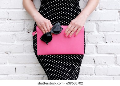 Fashion model woman in polka dots fitting dress posing with pink leather clutch bag and black sunglasses. Stylish accessory