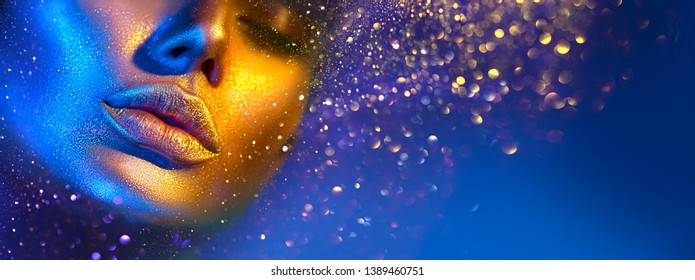 Fashion model woman skin face in bright sparkles, colorful neon lights, beautiful sexy girl lips, mouth. Trendy glowing gold skin make-up. Art design make up. Glitter metallic shine golden blue makeup