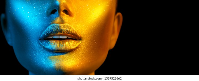 Fashion model woman skin face in bright sparkles, colorful neon lights, beautiful sexy girl lips, mouth. Trendy glowing gold skin make-up. Art design make up. Glitter metallic shine makeup Wide screen
