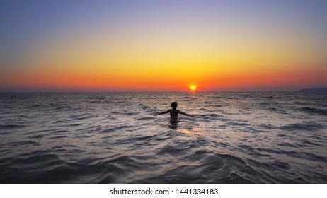 Fashion model woman walk out of ocean sunset water with hands wide open, FREEDOM CONCEPT, steadicam cinematic shot
