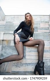 Modemodell. Junge blonde Kaukasierin in schwarzer Kleidung gekleidet. Schönes Kaukasisches Mädchen posiert draußen in Mailand, Italien. Straßenmode.