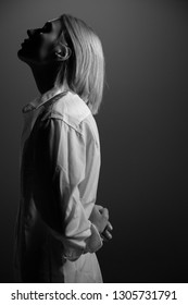 Fashion model. Young blond woman posing in studio wearing white shirt. Beautiful caucasian girl over gray background. Black and white