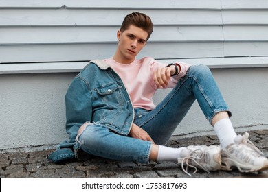 Fashion model young man in stylish denim jacket in ripped fashionable blue jeans in trendy white sneakers sit on stone tile near wall in city. Handsome guy in vintage casual clothes on street outdoors