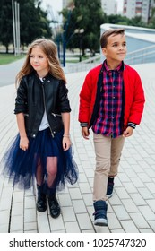 Fashion models children walk the stairs of the city streets. Boy and a girl, a blue skirt, a red jacket, a plaid shirt. Have a good time and attitude.