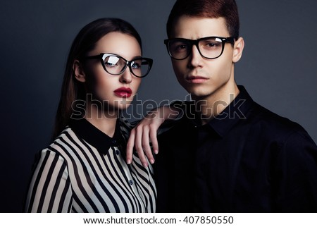 6a729f8e04c Fashion models couple wearing sunglasses. Sexy woman and handsome young man  portrait over dark background