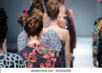 Fashion models on a runway during the fashion show finale.