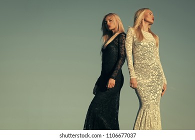 Fashion models. Opposites and contrasts concept. Women wearing black and white dresses. Fashion and beauty. Two girls with long blond hair posing on blue sky. Choice, decision and future, copy space