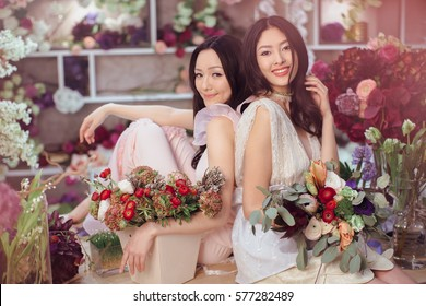 Fashion models in tender dresses posing and looking at camera. Beautiful asian florist girls making bouquet of flowers on table for sale against floral bokeh background in flower shop indoors. Two