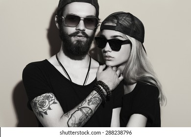 fashion monochrome portrait of beautiful couple together. Tattoo Hipster boy and girl. Bearded young man and blonde in sunglasses