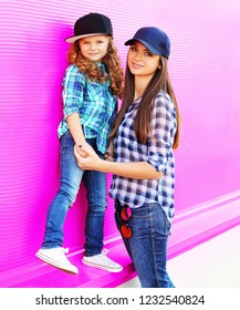 Fashion mother and child little girl in checkered shirts and baseball caps in city on colorful pink wall background