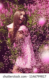Fashion, nature. Cheerful woman in dress with pink confetti around