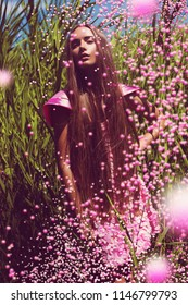 Fashion, nature. Fashionable woman in pink dress with flying flowers
