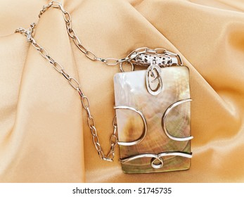fashion necklace with metal decoration over golden textile background