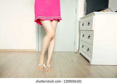 Fashion Nude Bow Sandals (Footwear) and Slim Legs in The Room. Female Sexy Long Legs. Beautiful Slim Legs Woman Standing with Nude Shoes and Pink Dress on Wooden Floor at Home Background