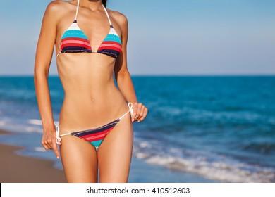 Fashion outdoor bodyshot portrait young sexy lady posing in bikini on sea background. Soft sunset bright.