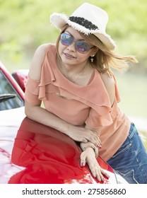 fashion outdoor photo of beautiful asian girl posing beside a red car