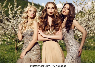 fashion outdoor photo of beautiful charming girls in luxurious sequin dresses posing in blossom spring garden
