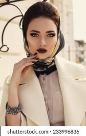 fashion outdoor photo of beautiful elegant lady wearing luxurious beige coat and silk scarf on her head