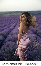 fashion outdoor photo of beautiful girl with blond hair in elegant clothes posing in summer flowering lavender field