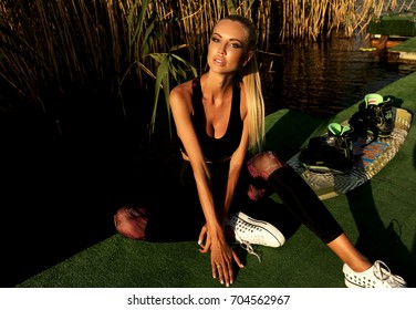 fashion outdoor photo of beautiful girl with blond hair in sport clothes posing at sunset beach with sports equipment