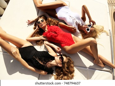 fashion outdoor photo of beautiful girls in elegant swimsuit relaxing on yacht in the sea