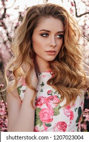 fashion outdoor photo of beautiful sensual girl with blond hair in elegant dress with floral print posing in blooming peach garden