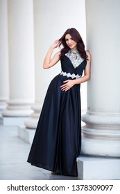 Fashion outdoor photo of beautiful sensual girl with dark hair in elegant dress posing in ancient architecture.