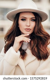 fashion outdoor photo of beautiful sensual woman with dark hair in elegant beige coat and white hat posing in the street