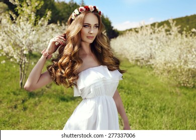 fashion outdoor photo of beautiful sensual woman with long red hair and flower's headband posing in spring blossom garden