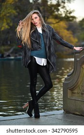Fashion outdoor photo of beautiful sensual woman with blonde hair wearing coat and leggings in the autumn park posing against the lake.