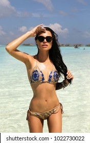fashion outdoor photo of beautiful sexy woman with dark hair in elegant bikini relaxing on tropical island