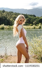 fashion outdoor photo of beautiful sexy woman with blond hair in elegant swimming suit posing in nice nature place, a lake surrounded by mountains