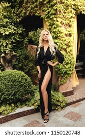 fashion outdoor photo of beautiful sexy woman with blond hair in elegant black dress posing in luxurious villa